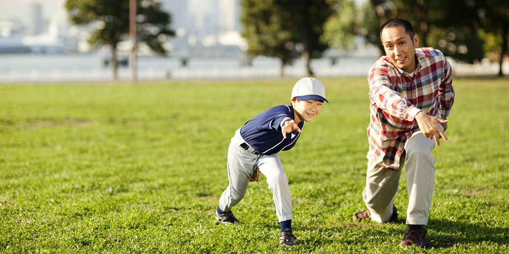 Father and son throwing baseball as part of his chiropractic and physical therapy treatment